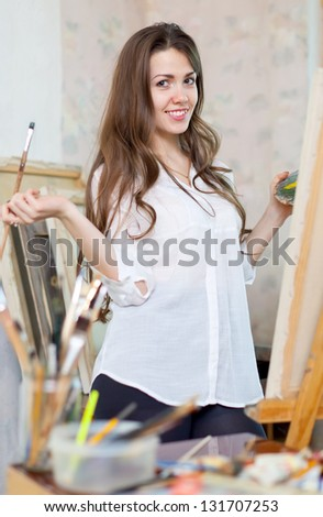 Long-haired girl paints with oil colors on easel