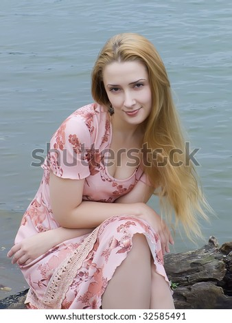 LONG-HAIRED GIRL SITTING BY THE RIVER