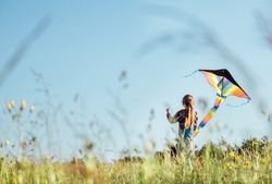 Long-haired Girl with flying a colorful kite on the high grass meadow in the mountain fields. Happy childhood moments or outdoor time spending concept image.