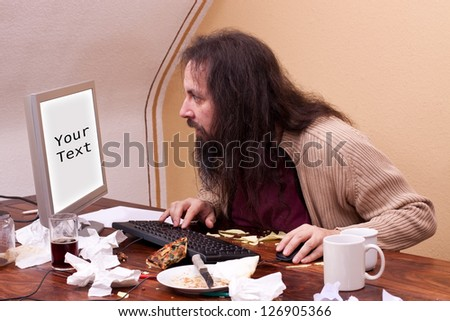 long haired nerd looks at monitor with space for text