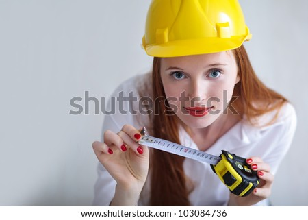 Long haired red headed woman holding a tape measure and wearing a safety hat