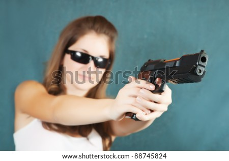 Long-haired teen girl aiming a black gun. Focus on gun only