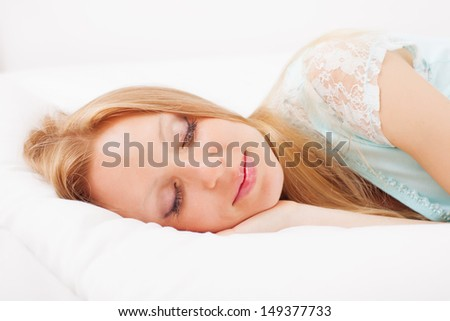 Long-haired woman sleeping on white sheet