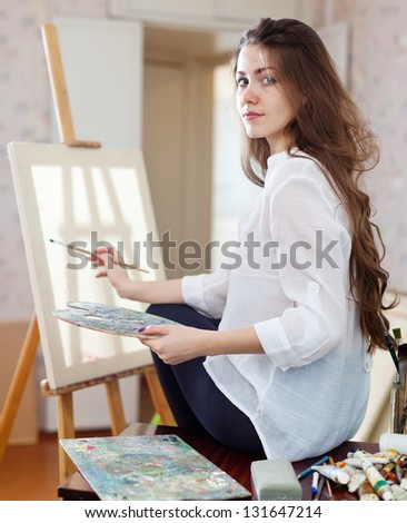 Long-haired woman with oil colors and brushes near easel with blank canvas ready for job  in workshop