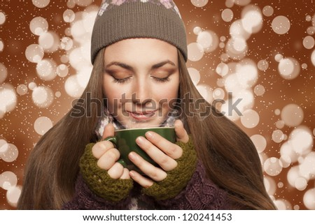 long haired young woman relaxing and warming with cup of coffee or tea brown background with bokeh and sparkles