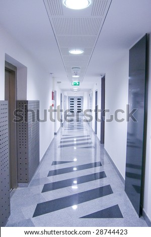 Long hallway in corporate building with doors at the end.