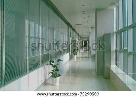 Long hallway in the modern office building with windows
