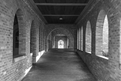 Long Hallway with Light coming Through Arch Brick Windows in black and white.