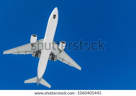 long haul widebody white passenger airplane on a blue sky background. bottom view a few seconds before landing. composition photography. flying overhead towards destination airport. travel concept. #1060405445