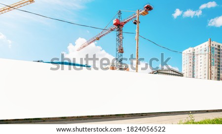 long hoarding with empty space for mock up on construction site red crane and blue sky background outside ストックフォト ©