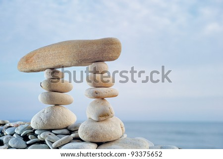 Long horizontal stone between a piles of pebble