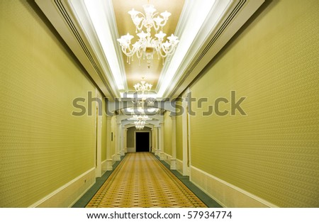 Long hotel corridor with  carpet and green wallpaper
