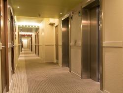 long hotel corridor with doors and elevator