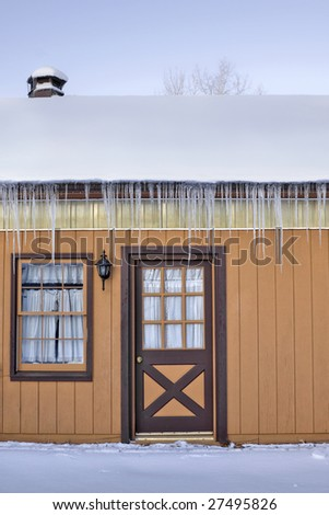 Long icicles hanging from the side of a home covered with snow.
