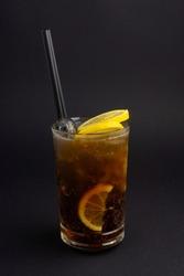 Long Island Ice Tea cocktail on black background