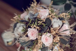 Long lasting flowers decoration. Preserved roses with dried flowers bouquet closeup. Selective focus on home decoration made of decorative plants. Eternal, stabilized, forever rose flower.