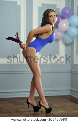 long legs girl standing in high heels with balloons at background