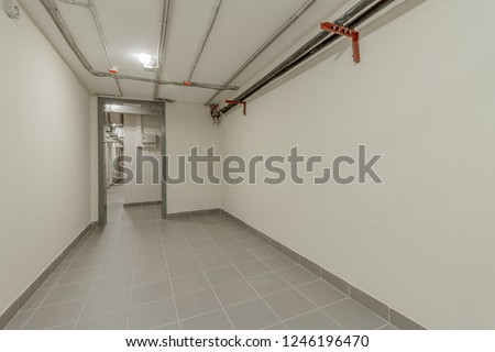 LONG LIGHT CORRIDOR WITH IRON AND STEEL DOORS AND COMMUNICATIONS UNDER CEILING IN BASEMENT OF MODERN RESIDENTIAL BUILDING. Bomb shelter (shelter, bombproof shelter, bombshelter, air-raid shelter).