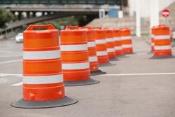 long line of orange traffic barrier barrels to detour traffic