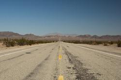 long lonely old asphalt road Route 66 in Arizona and blue sky, lange einsame alte Route 66 im Bundesstaat Arizona mit blauen Himmel