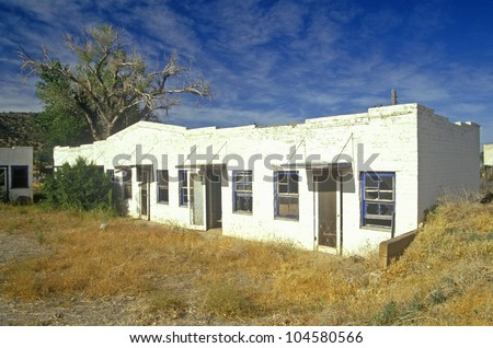 Long,  low abandoned motel with weeds on Route 66