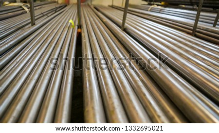 Long metal pipes stored in the room of the steel factory ready for production
