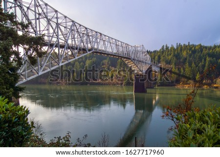 Long metal structured bridge, spanning a large river.