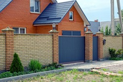 Long modern brown fence made of bricks and iron on the street in front of the road