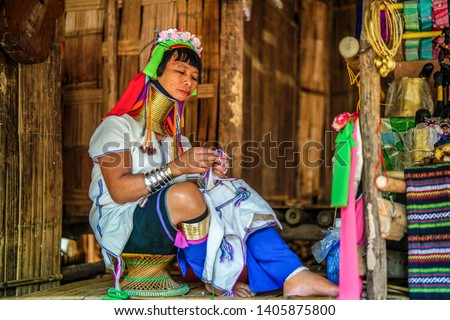 Long-neck Asian Kayan Padaung woman working and sewing in tribal village. Beautiful portrait of woman with neck rings brass coils at work