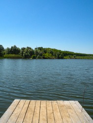 Long Old wooden pier and beautiful lake. Empty on small country lake. of summer. Place for text