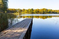 Long pier and a calm lake, with a house far away.