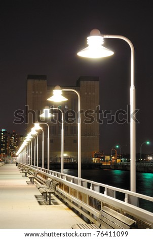 Long pier with lights in the distance.