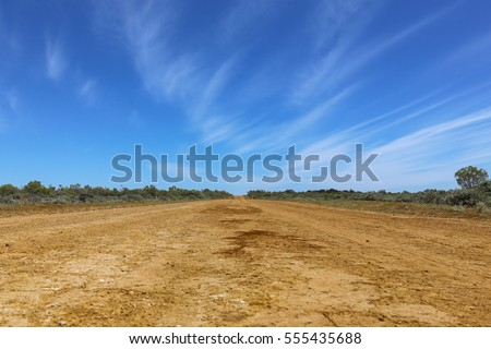 Long red dusty road in the Australian outback #555435688