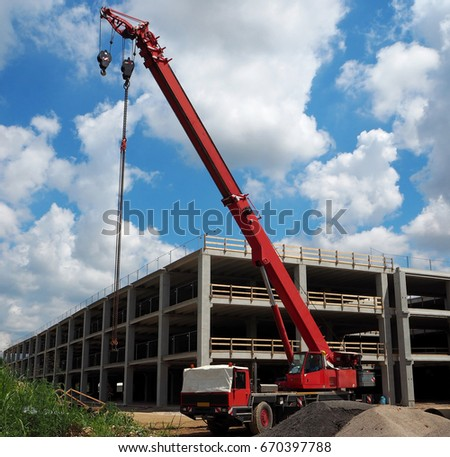 Long red telescopic crane on truck in a construction site under blue sky with clouds.  Building activity, new area development