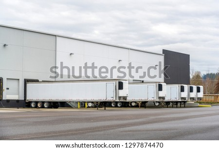 Long refrigerator semi trailers stand in row in warehouse docks with gates and loading and unloading commercial cargo and continuing go to the destination according to schedule