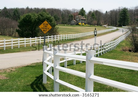 long road with fences and sign - stock photo