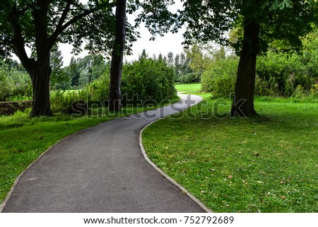 Long road with green field in the park - Shutterstock ID 752792689