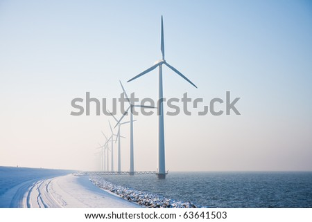 Long row of snowy windmills standing in Dutch sea disappearing in winter haze