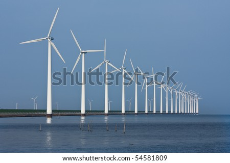 Long row of windmills, mirrored in the Dutch sea - stock photo