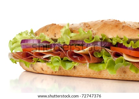 Long sandwich with ham, cheese, tomatoes, red onion and lettuce. Closeup, isolated on white. Another angle available