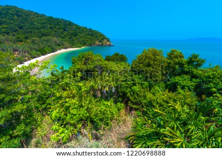 Long sandy beach and turquoise Adaman Sea from lush thick green tropical forest with lush foliage against a bright blue sky without clouds. Lanta National Park, Krabi, Thailand.