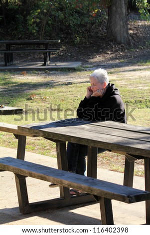 Long shadows and strong back light add interest to image of silver-haired senior woman relaxing at park bench in evening warmth.