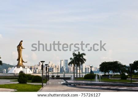 long shot of Guan Yim statue in front of city, macau