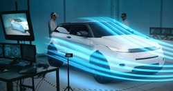 Long shot of scientists using vr technology to simulate aerodynamic properties of car