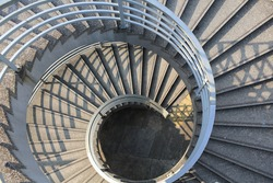 long spiral stair of footbridge with the sun ray light and shadow in daytime detail , in Central, hong kong