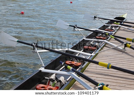 Long sport boat with oars stands at wooden pier at sunny day.