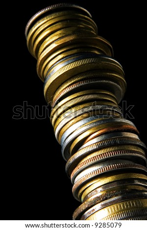 long stack of coins from below on black background