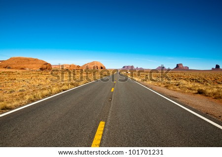 Long straight road crossing the famous Monument Valley.