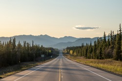 Long straight road heading towards large mountains in Yukon Territory, northern Canada in the spring time on the Alaska Highway.