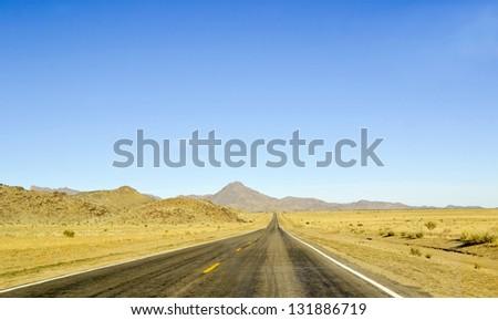 Long, straight road with horizon blue sky and mountains. Grand Canyon. Arizona. USA